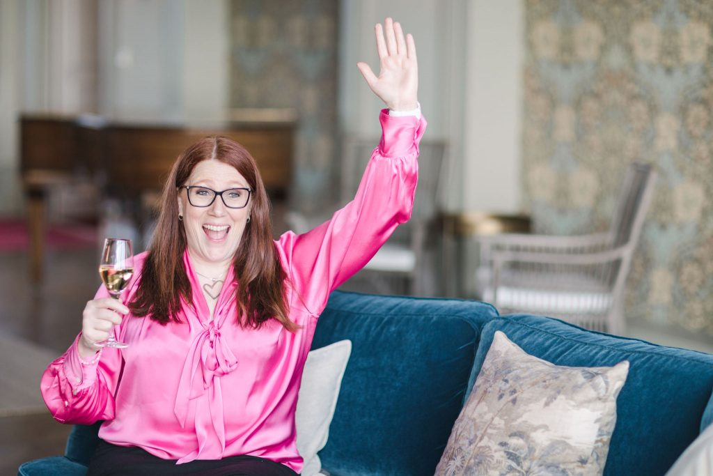 Woman in cerise tied front blouse with a glass of champagne in one hand and raises the other hand in a happy hello