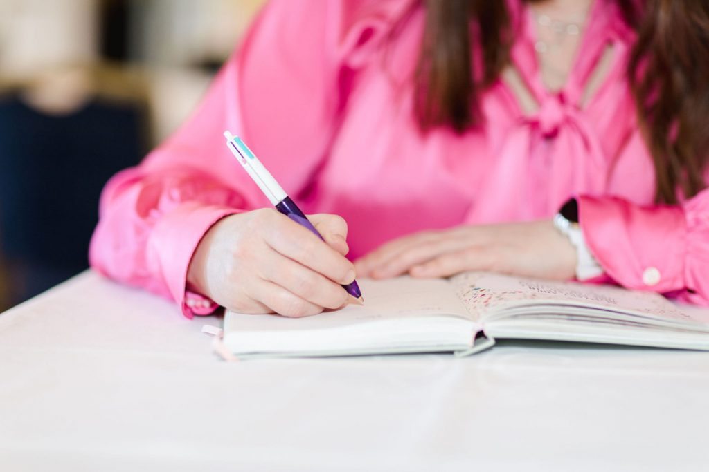 Woman in cerise blouse writing journal by hand