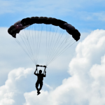Parachuting with blue sky and white, fluffy clouds